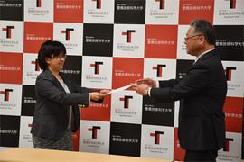井上理事・副学長から修了証書を授与される研修代表者