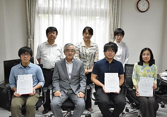 大貝彰 理事・副学長を囲む受賞者(前列)と男女共同参画推進本部員(後列)