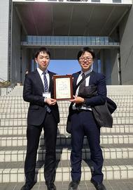 授賞式が行われた芝浦工業大学豊洲キャンパスで賞状を持つ坂本さん(左)と永井萌土講師(右)