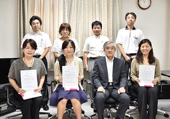大貝彰 理事・副学長を囲む受賞者(前列)と男女共同参画推進室員(後列)
