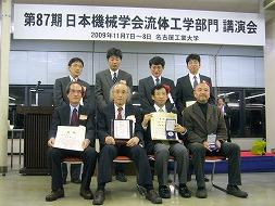 賞状を持つ飯田教授