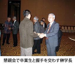 懇親会で卒業生と握手を交わす榊学長
