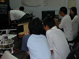 学生に教えてもらいながら、ロボットのプログラムを作成する受講生